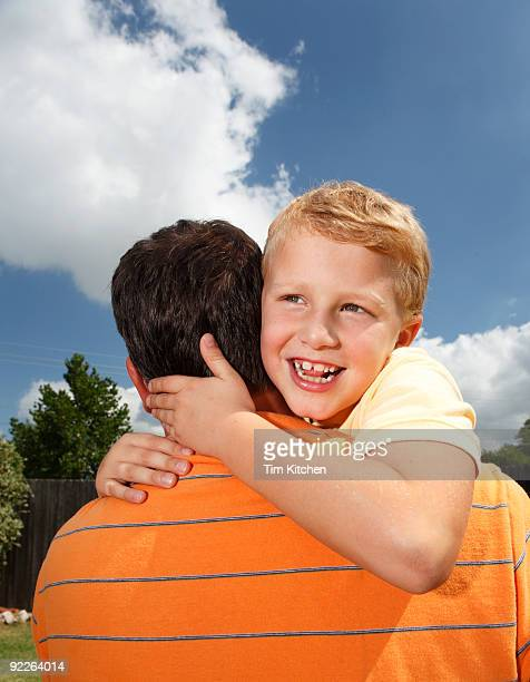 Son hugging father, smiling