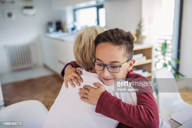 son hugging mom - human relationship stock pictures, royalty-free photos & images
