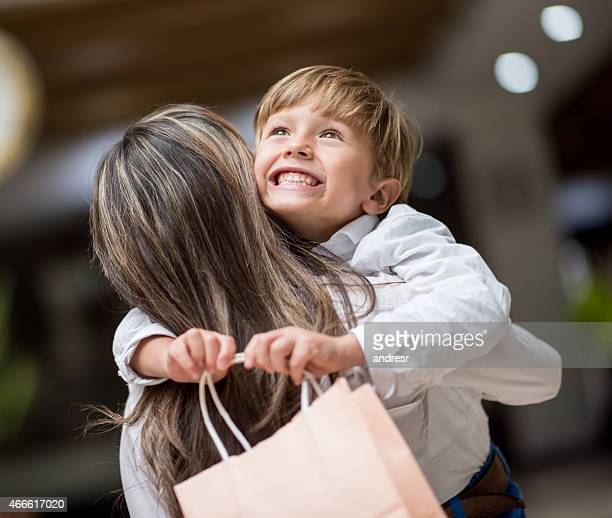 Son hugging mother at the shopping center