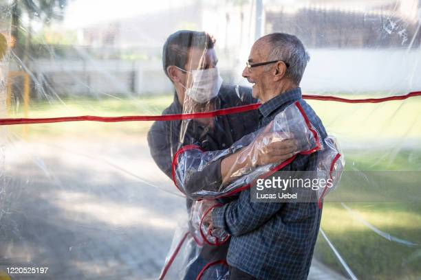 Son hugs his father at the Geriatric Clinic Três Figueiras on June 16, 2020 in Gravatai, Brazil. The clinic created the Tunel do Abraco for elderly...