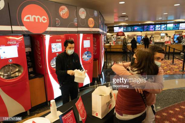 Son hugs his mother as a concessions worker hands over napkins and soda inside the AMC movie theater at the Westfield Century City shopping mall in...