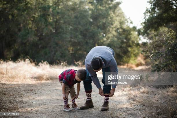 son imitating father in adjusting socks on field - adjust socks stock pictures, royalty-free photos & images