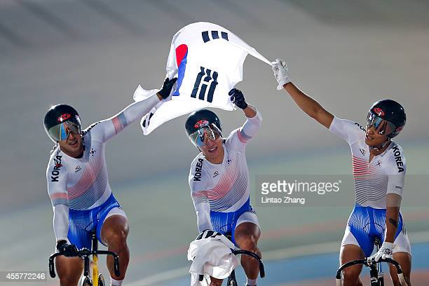 Son Jeyong Kang Dongjin and Im Chaebin of South Korea celebrate after winning the Cycling Track Men's Team Sprint Final during the 2014 Asian Games...