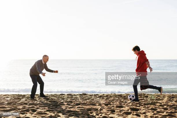 son kicking soccer ball while father defending at beach against clear sky - top garment stock pictures, royalty-free photos & images