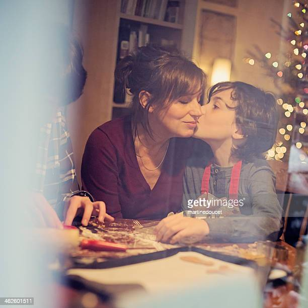 Son kissing mother while making cookies, shot through window.