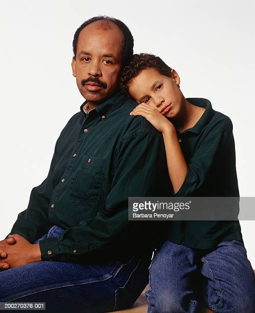 Son (12-13) leaning on back of father, portrait