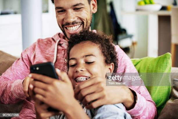 son looking at photos on smartphone with dad - north african ethnicity stock pictures, royalty-free photos & images