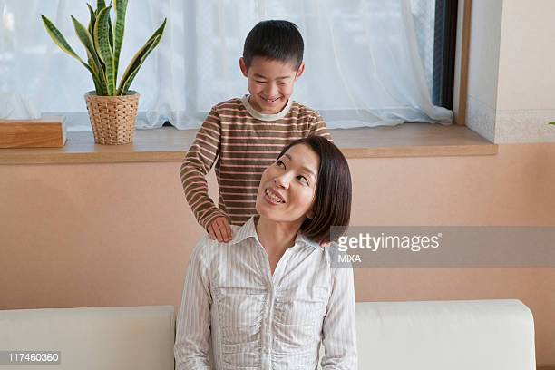 son massaging mother's shoulder - japan mom and son stock photos and pictures