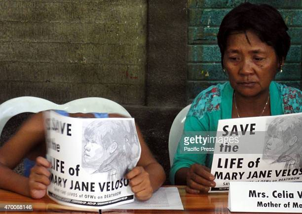 A son of convicted drug trafficker Mary Jane Veloso hangs his head down as Celia Veloso mother of Mary Jane listens during a press conference at the...