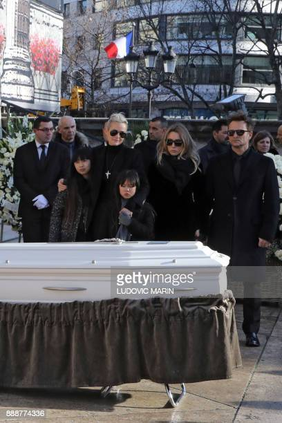 Son of late French singer Johnny Hallyday David Hallyday daughter Laura Smet Johnny's wife Laeticia their daughters Jade and Joy stand by the coffin...