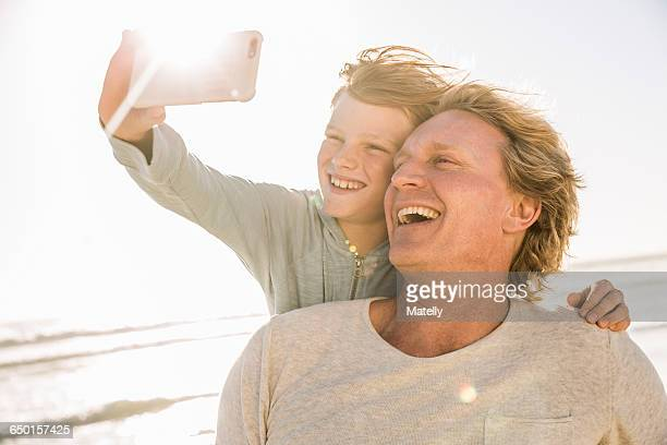 Son on beach using smartphone to take selfie smiling