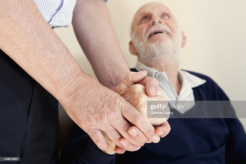 Son patting fathers hand : Stock Photo