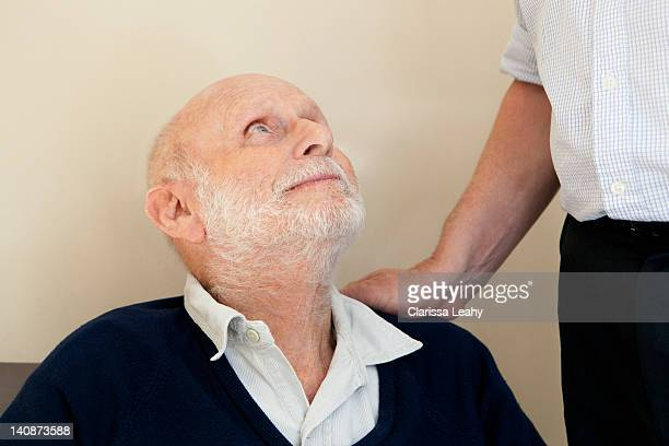 son patting fathers shoulder - vulnerability stock photos and pictures