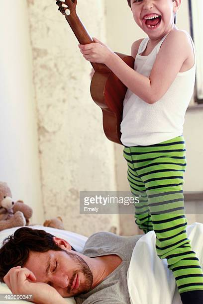 Son playing guitar whilst his father sleeps
