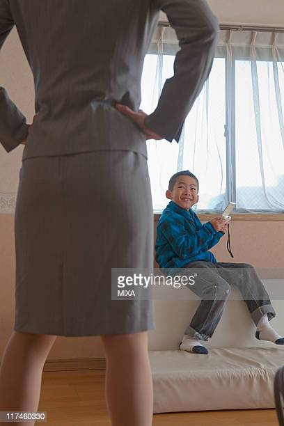 son playing handheld video game and mother scolding it - 説教 ストックフォトと画像