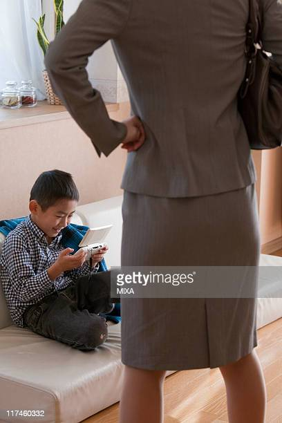 Son playing handheld video game and mother scolding it