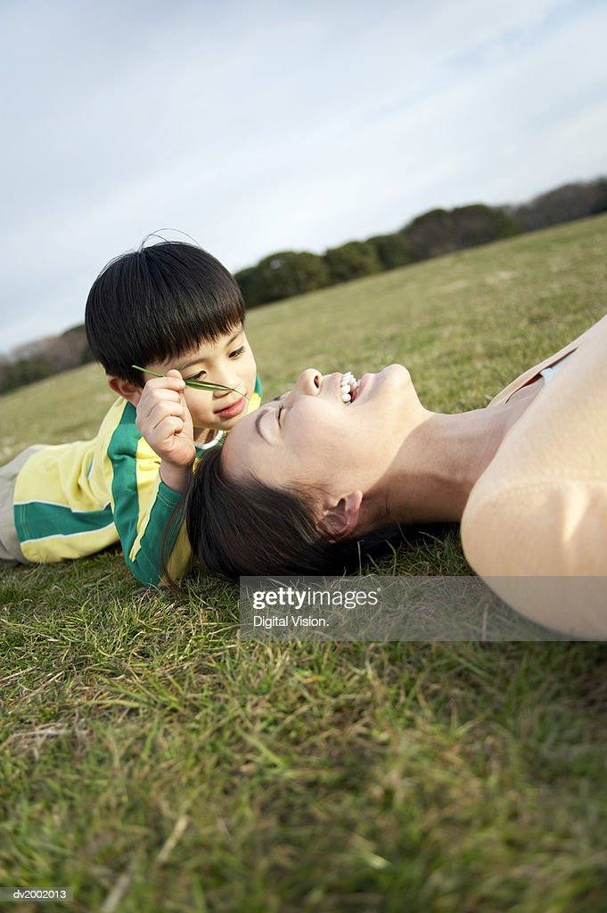 Son Playing Holding a Blade of Grass Across His Mothers Face : Stock Photo