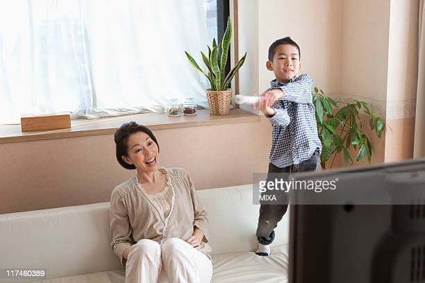 Son playing video game and mother looking it