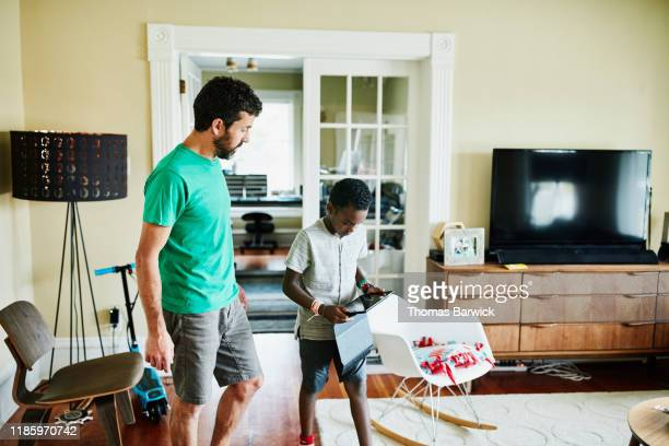 son preparing to show father video on digital tablet in living room - insight tv stock pictures, royalty-free photos & images