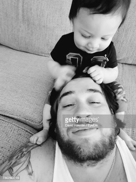 Son Pulling Father Hair While Sitting On Sofa At Home