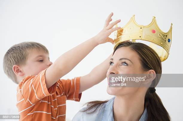 Son (6-7) putting crown to mothers head