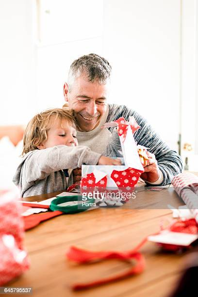 Son removing gift from box by father at table