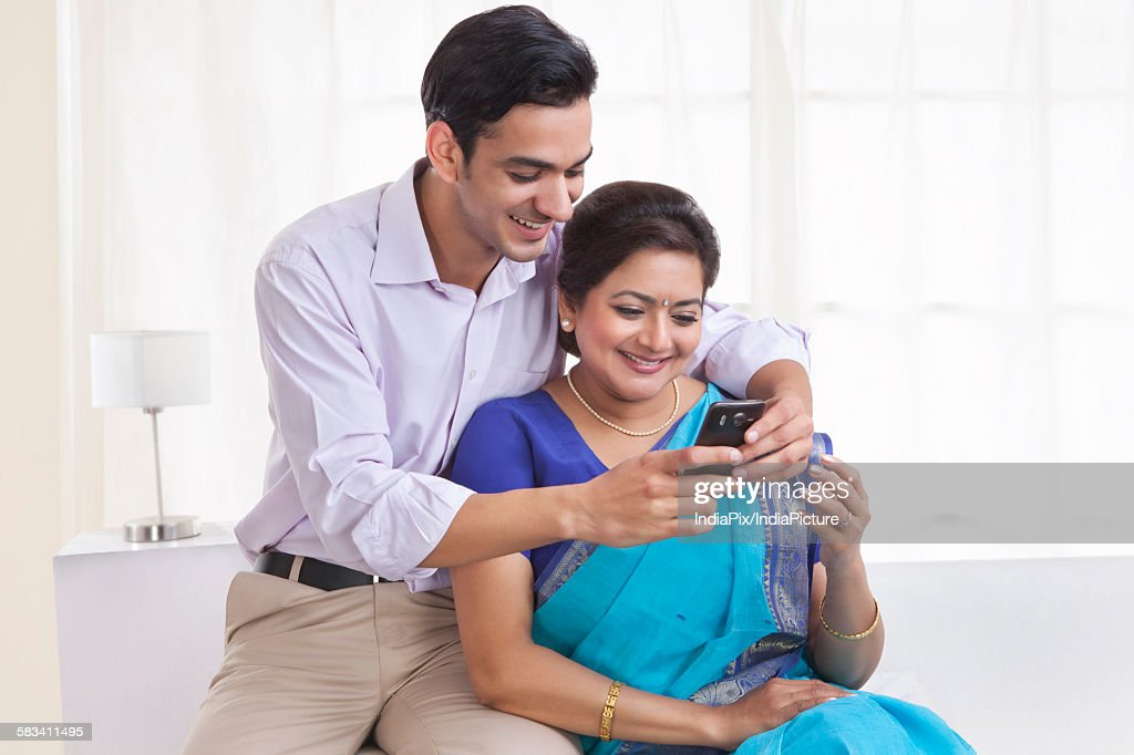 Son showing mother a picture on mobile phone : Stock Photo