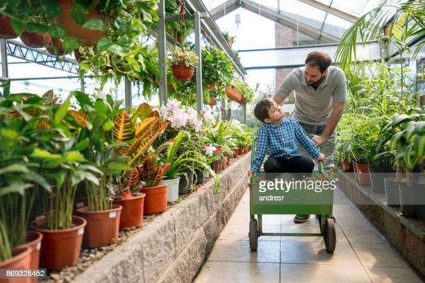 Son sitting on a cart and dad pushing it through the garden center looking happy