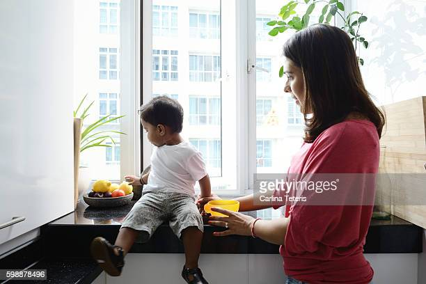 Son sitting on a kitchen counter ignoring his mom trying to feed him
