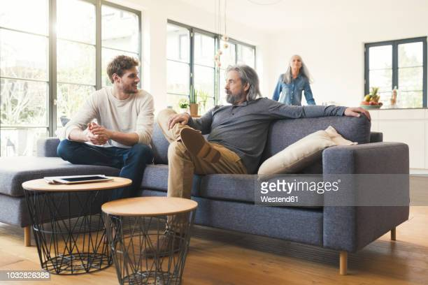 son sitting on couch, talking to his father - volwassen nageslacht stockfoto's en -beelden