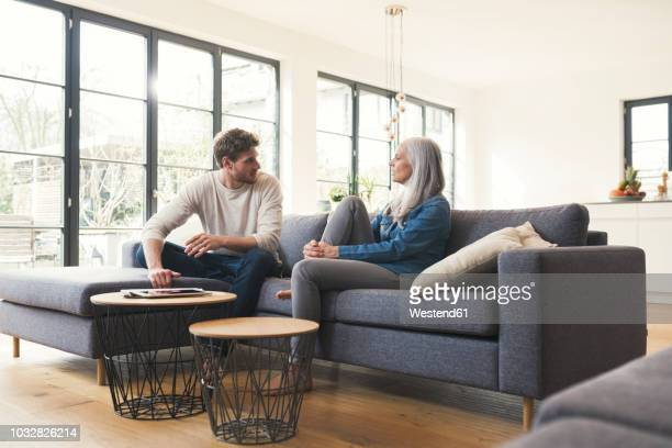 son sitting on couch, talking to his mother - mother and son stock photos and pictures