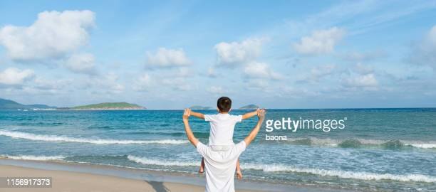 zoon zittend op vaders schouders genieten van het strand - menselijk gewricht stockfoto's en -beelden