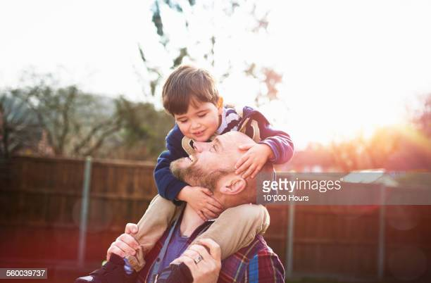 son sitting on father's shoulders - father stock pictures, royalty-free photos & images