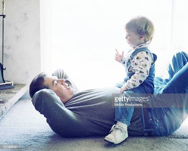 Son (1-2) sitting on father's stomach