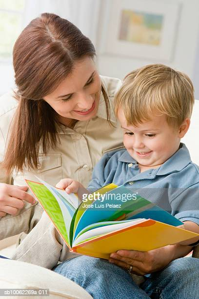 Son (3-4) sitting on mother lap  with book, smiling
