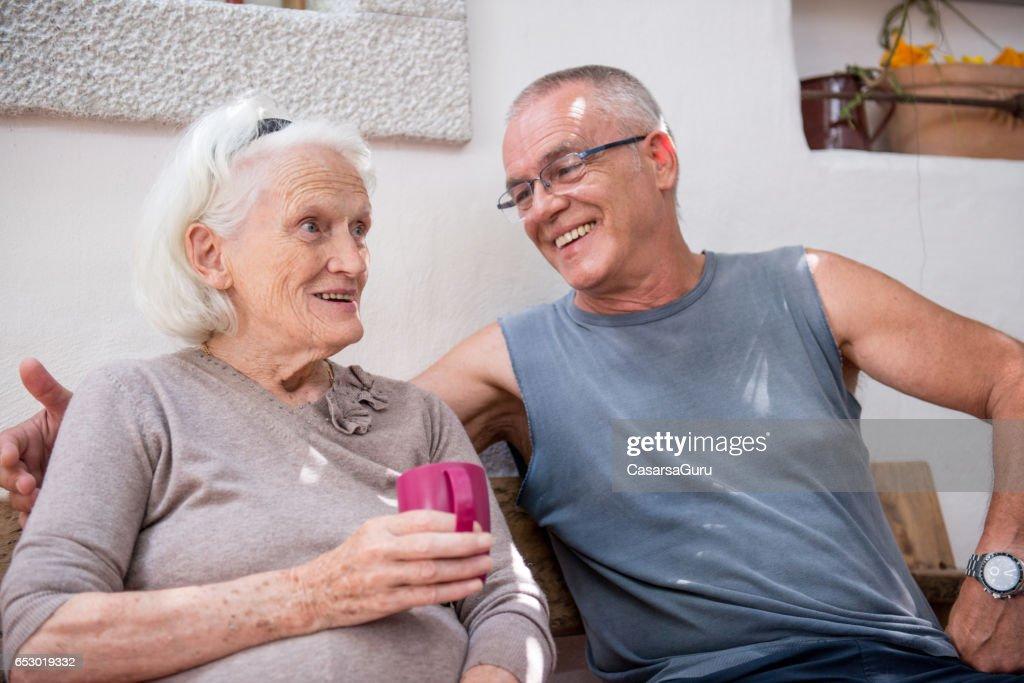 Nemen van koffie met haar Senior moeder zoon : Stockfoto