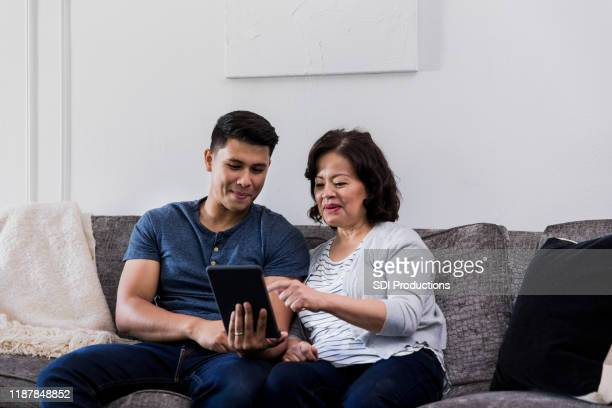 son teaches senior mother how to use digital tablet - zia e nipote foto e immagini stock
