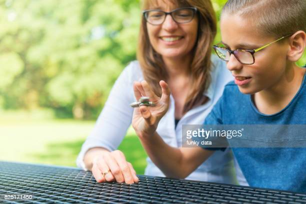 Son teaching mother fidget spinner