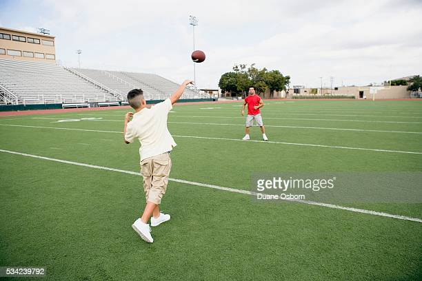 Son Throwing Football to Father