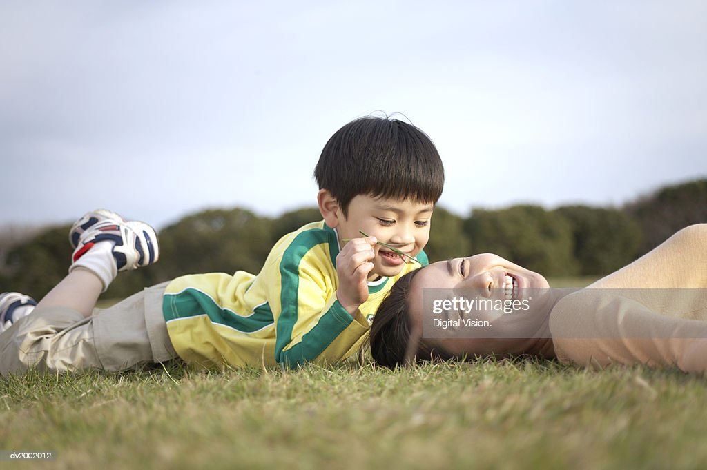 Son Tickling His Mothers Face with a Blade of Grass : Stock Photo