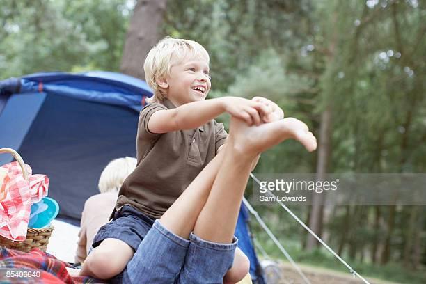 filho fazendo cócegas mães pé na área de acampamento - fazendo cócegas - fotografias e filmes do acervo