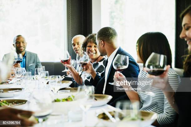 Son toasting mother during celebration meal in restaurant with family and friends