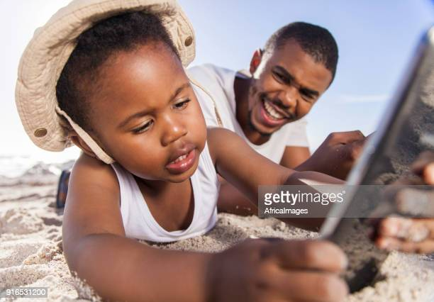 Son using a digital tablet while his father looks on and smiles.