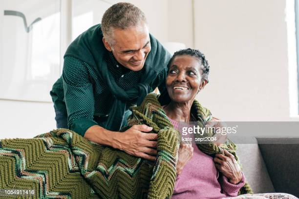 son visiting  mother in retirement home - dementia stock pictures, royalty-free photos & images