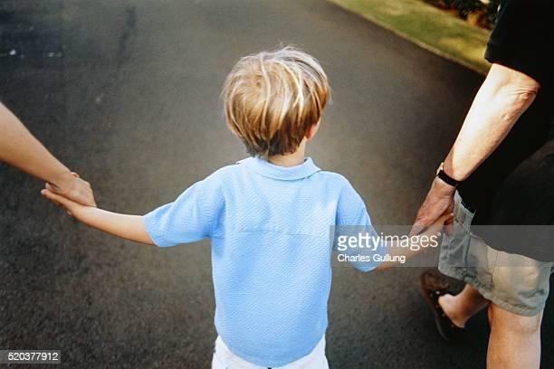 Son Walking Between Parents Hand in Hand