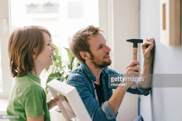 son watching father driving a nail into the wall at home - hammer stock pictures, royalty-free photos & images