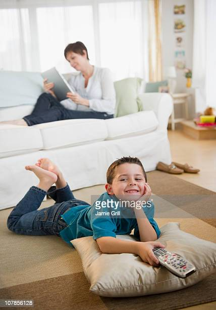 Son watching TV, while mother reads on e-reader