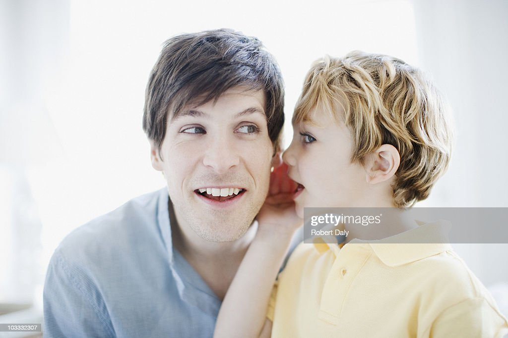 Son whispering in fathers ear : Stock Photo