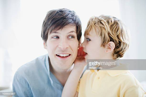 Son whispering in fathers ear