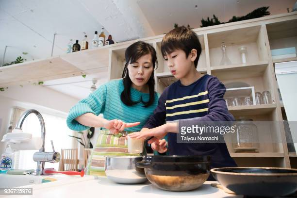 son who helps mother's cooking - zakelijke kleding stock pictures, royalty-free photos & images